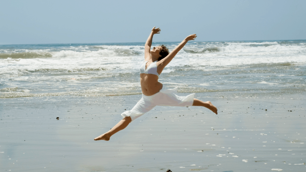 Woman Celebrating dancing on the beach